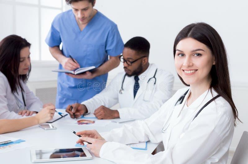 Ομάδα των γιατρών που διοργανώνουν τη συνεδρίαση στο ιατρικό γραφείο στοκ εικόνες