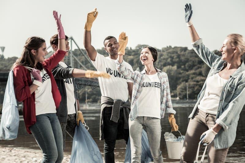 Ομάδα των ενεργών εθελοντών που αισθάνονται εύθυμων και εμπνεσμένων εργαζόμενη από κοινού στοκ φωτογραφία με δικαίωμα ελεύθερης χρήσης
