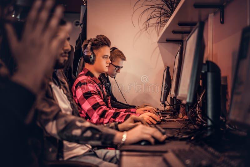Ομάδα των εφηβικών παιχνιδιών gamers σε ένα τηλεοπτικό παιχνίδι multiplayer στο PC σε μια λέσχη τυχερού παιχνιδιού στοκ φωτογραφία