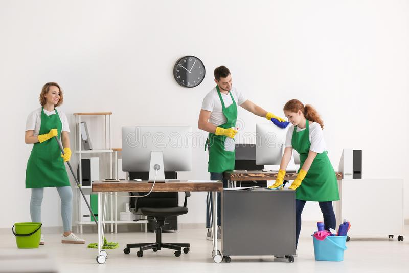 Ομάδα των νέων καθαρίζοντας επαγγελματιών υπηρεσιών στην εργασία στοκ εικόνα με δικαίωμα ελεύθερης χρήσης