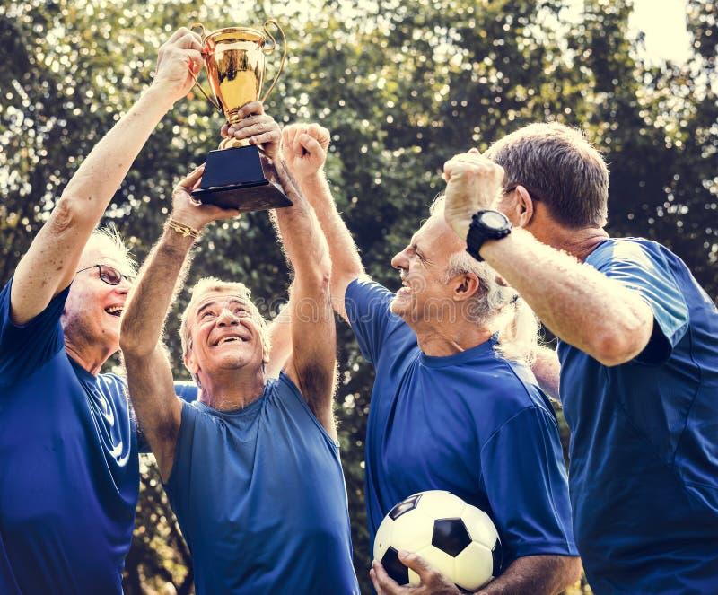 Ομάδα των ώριμων ποδοσφαιριστών που κερδίζουν το κύπελλο στοκ φωτογραφίες με δικαίωμα ελεύθερης χρήσης