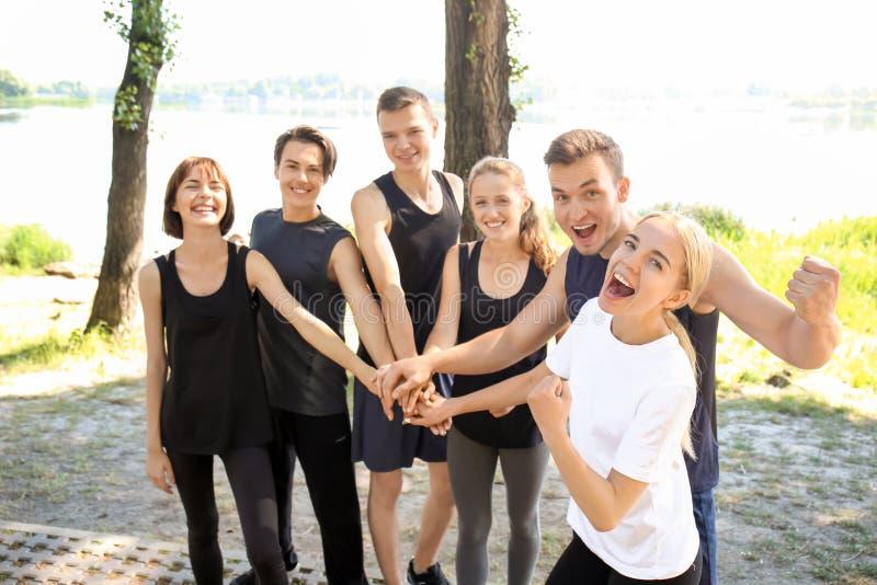 Ομάδα φίλαθλων νέων που βάζουν τα χέρια μαζί υπαίθρια στοκ εικόνες με δικαίωμα ελεύθερης χρήσης