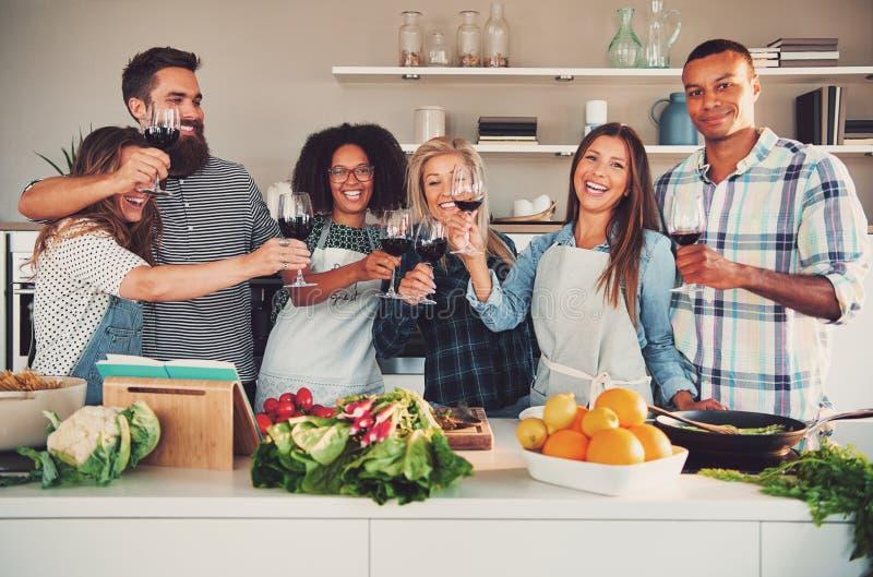 Ομάδα φίλων ενθαρρυντικών στην κουζίνα στοκ εικόνα με δικαίωμα ελεύθερης χρήσης