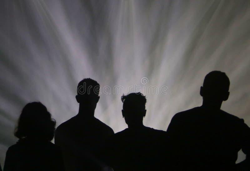Ομάδα φίλων κάτω από τα σκηνικά φω'τα κατά τη διάρκεια μιας επίδειξης στο φεστιβάλ σόναρ στη Βαρκελώνη στοκ εικόνες