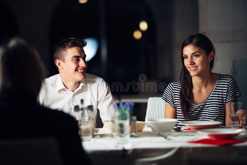 Ομάδα φίλων που έχουν ένα γεύμα σε ένα εστιατόριο Διπλή ημερομηνία Ελκυστική νύχτα ανθρώπων έξω, που δειπνεί σε ένα ξενοδοχείο άν στοκ εικόνα