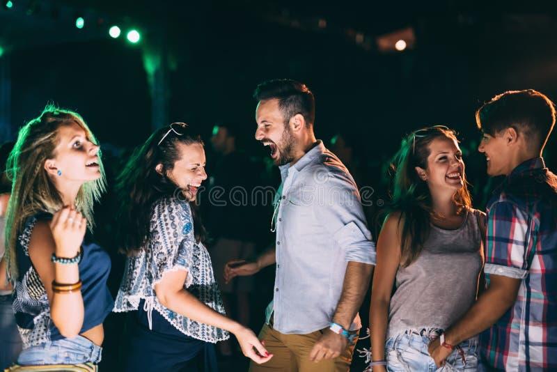 Ομάδα φίλων που έχουν τη διασκέδαση και που χορεύουν στη συναυλία στοκ φωτογραφία