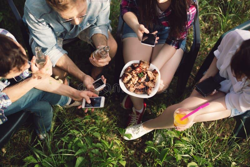 Ομάδα φίλων που έχουν το πικ-νίκ στο πάρκο στοκ εικόνα με δικαίωμα ελεύθερης χρήσης