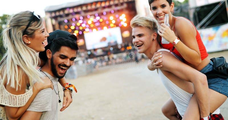 Ομάδα φίλων που έχουν το χρόνο διασκέδασης στο φεστιβάλ μουσικής στοκ εικόνες