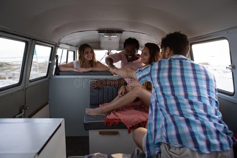 Ομάδα φίλων που δίνουν την πρόσκρουση πυγμών στο φορτηγό τροχόσπιτων στην παραλία στοκ εικόνα με δικαίωμα ελεύθερης χρήσης