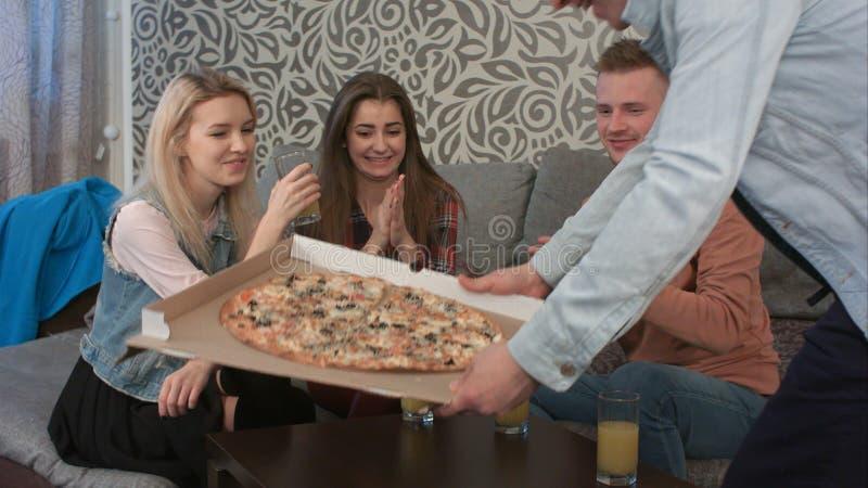 Ομάδα φίλων που μιλούν, όταν ο φίλος τους που φέρνει τη take-$l*away πίτσα στοκ εικόνες