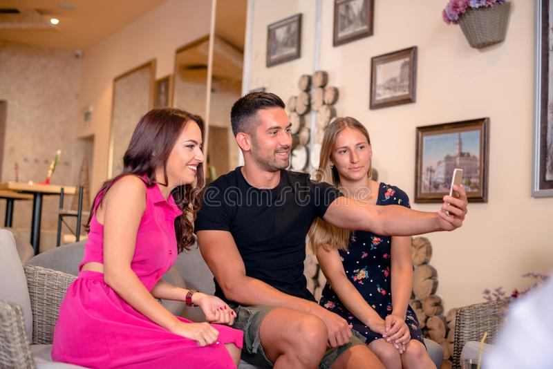 Ομάδα φίλων που παίρνουν τις φωτογραφίες σε έναν καφέ στοκ εικόνα με δικαίωμα ελεύθερης χρήσης