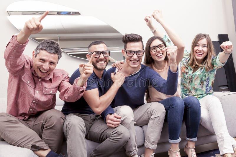 Ομάδα φίλων που προσέχουν έναν αγώνα ποδοσφαίρου στη TV στον καναπέ στοκ εικόνες με δικαίωμα ελεύθερης χρήσης