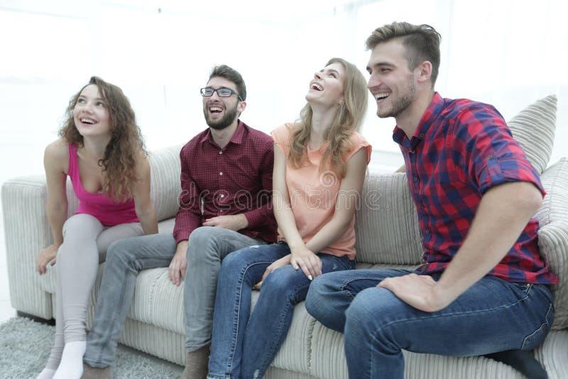 Ομάδα χαμογελώντας νέων που κάθονται στον καναπέ στοκ φωτογραφία με δικαίωμα ελεύθερης χρήσης
