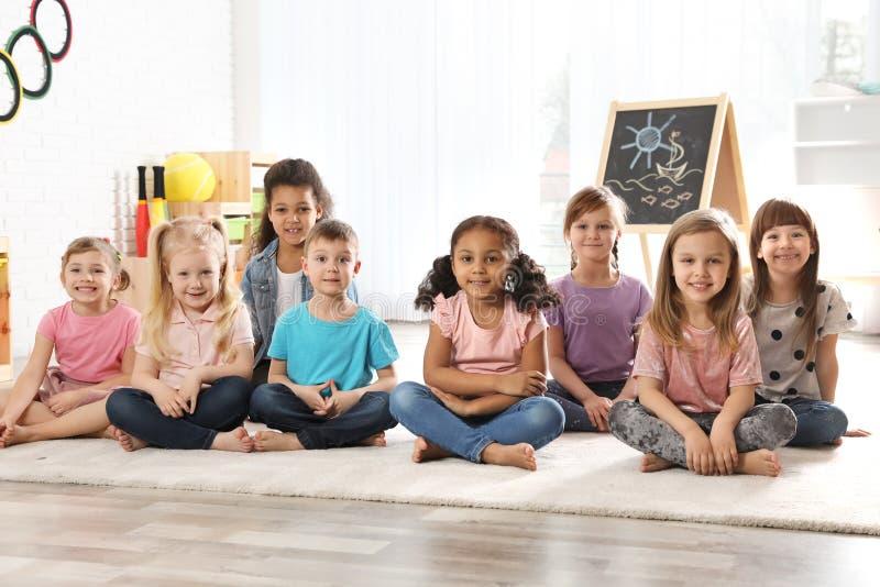 Ομάδα χαριτωμένων μικρών παιδιών που κάθονται στο πάτωμα Δραστηριότητες χρόνου ψυχαγωγίας παιδικών σταθμών στοκ φωτογραφία