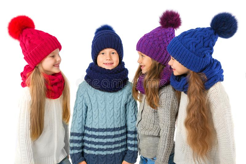 Ομάδα χαριτωμένων παιδιών στα χειμερινά θερμά καπέλα και μαντίλι στο λευκό Χειμερινά ενδύματα παιδιών στοκ φωτογραφία με δικαίωμα ελεύθερης χρήσης
