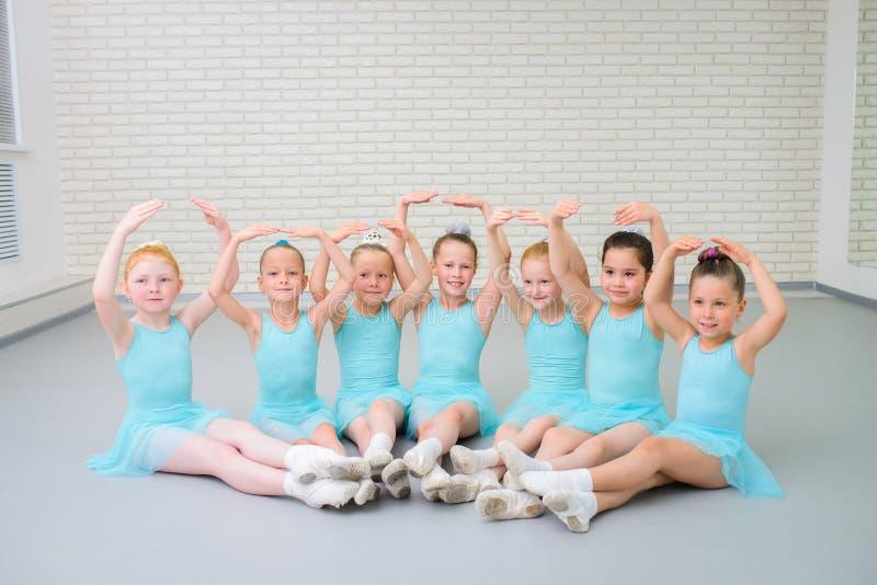 Ομάδα χαριτωμένων χορευτών λίγου μπαλέτου που εξετάζουν τη κάμερα στη σχολική τάξη χορού στοκ φωτογραφία με δικαίωμα ελεύθερης χρήσης