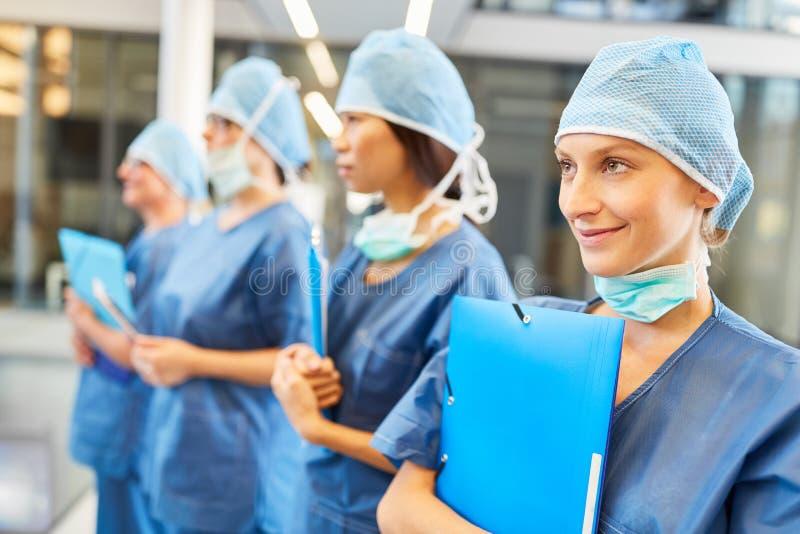 Ομάδα χειρουργικών επεμβάσεων με το νέο θηλυκό γιατρό στην κατάρτιση στοκ εικόνα με δικαίωμα ελεύθερης χρήσης