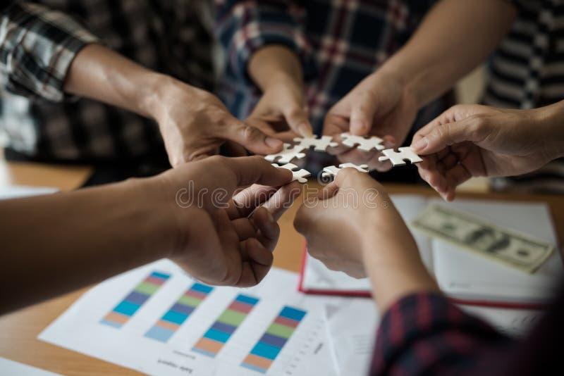 Ομάδα χεριών επιχειρηματιών που συγκεντρώνουν το λευκό γρίφων τορνευτικών πριονιών Β στοκ εικόνα με δικαίωμα ελεύθερης χρήσης