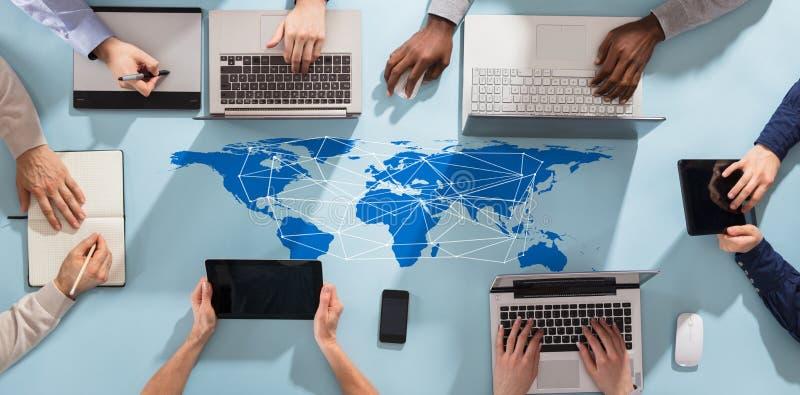 Ομάδα Businesspeople που εργάζεται με τις ηλεκτρονικές συσκευές στοκ φωτογραφία