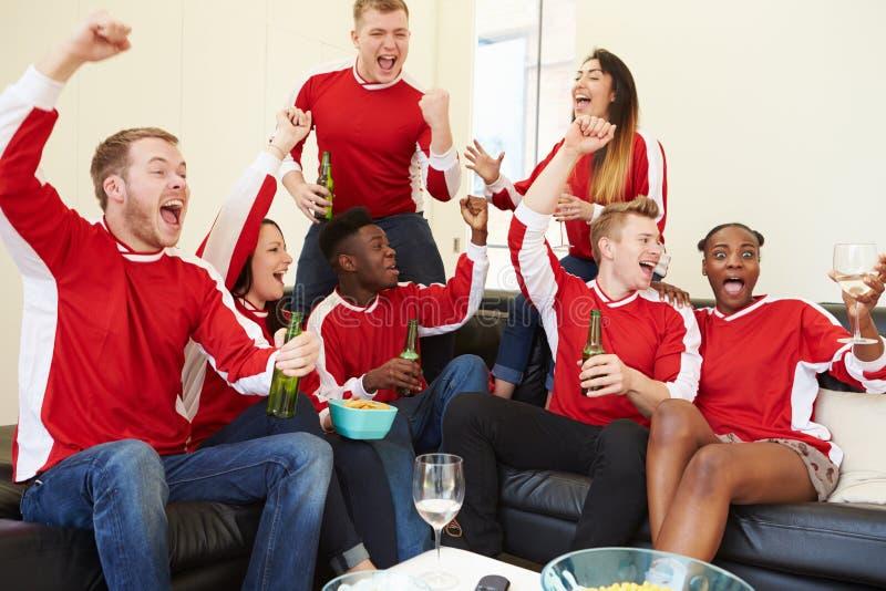 Ομάδα αθλητικών ανεμιστήρων που προσέχει το παιχνίδι στη TV στο σπίτι στοκ φωτογραφία