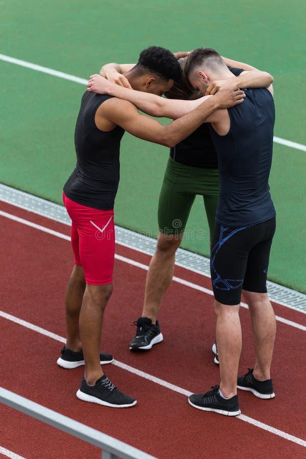 Ομάδα αθλητών Multiethnic που στέκεται να τρέξει τη διαδρομή υπαίθρια στοκ εικόνα