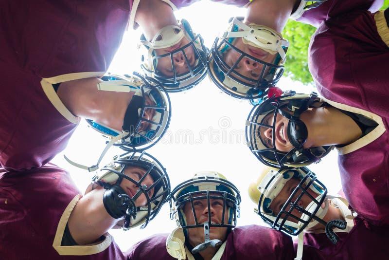 Ομάδα αμερικανικού ποδοσφαίρου που έχει τη συσσώρευση στην αντιστοιχία στοκ φωτογραφία με δικαίωμα ελεύθερης χρήσης