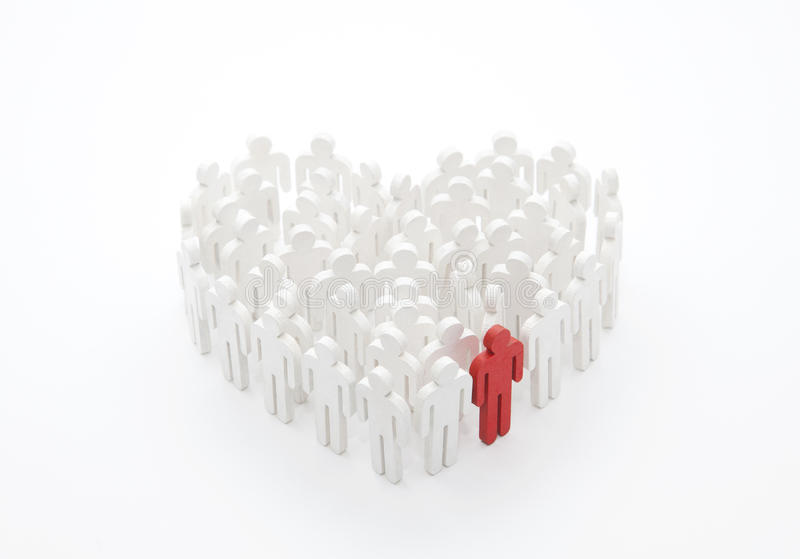 Ομάδα ανθρώπων με μορφή μιας καρδιάς με ένα κόκκινο άτομο στοκ φωτογραφία