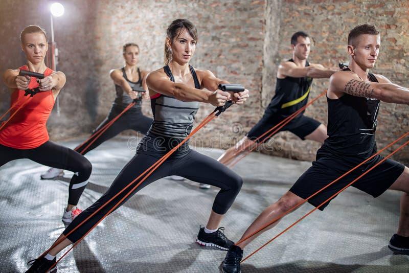 Ομάδα ανθρώπων που κάνει workout με την ελαστική ζώνη στοκ εικόνα με δικαίωμα ελεύθερης χρήσης