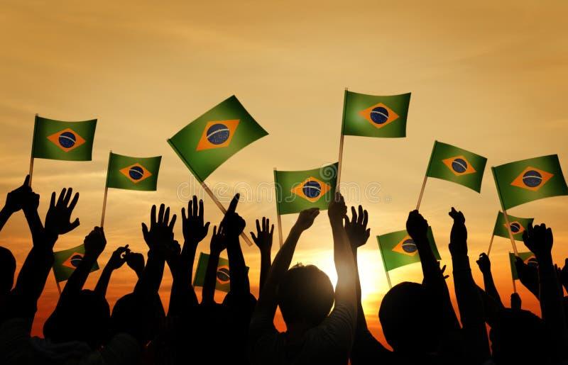 Ομάδα ανθρώπων που κυματίζει τις βραζιλιάνες σημαίες σε πίσω LIT στοκ εικόνες