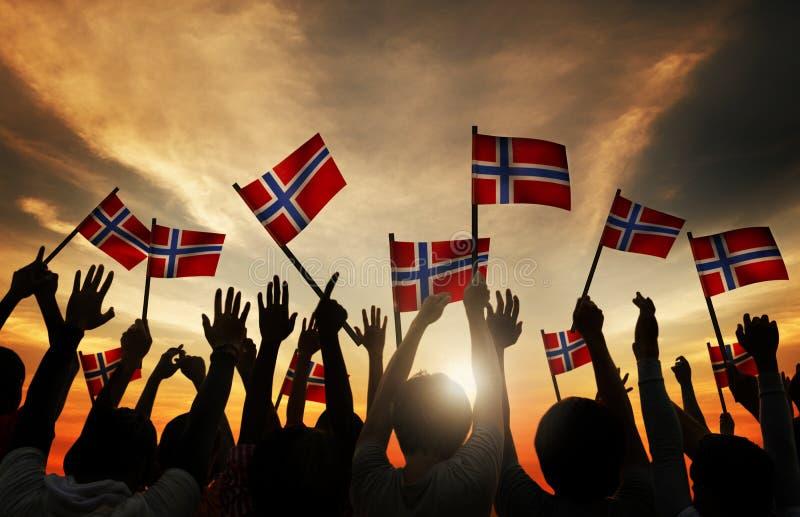 Ομάδα ανθρώπων που κυματίζει τις νορβηγικές σημαίες σε πίσω LIT στοκ φωτογραφίες με δικαίωμα ελεύθερης χρήσης