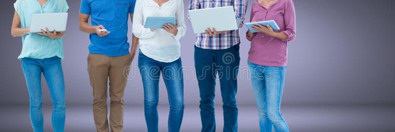 Ομάδα ανθρώπων που στέκεται με τις συσκευές lap-top και ταμπλετών και το υπόβαθρο σύντομων χρονογραφημάτων στοκ φωτογραφία