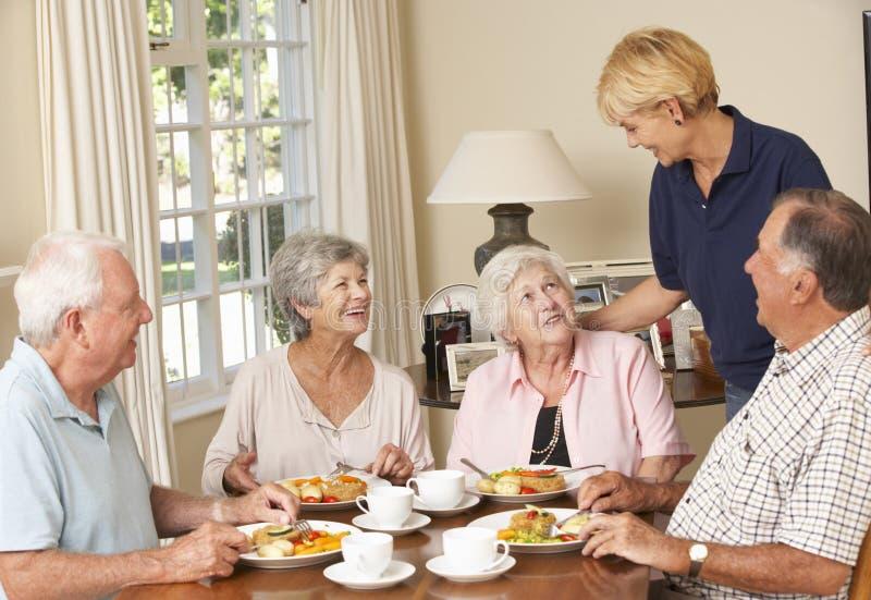 Ομάδα ανώτερων ζευγών που απολαμβάνουν το γεύμα μαζί στο σπίτι προσοχής με την εγχώρια βοήθεια στοκ φωτογραφία