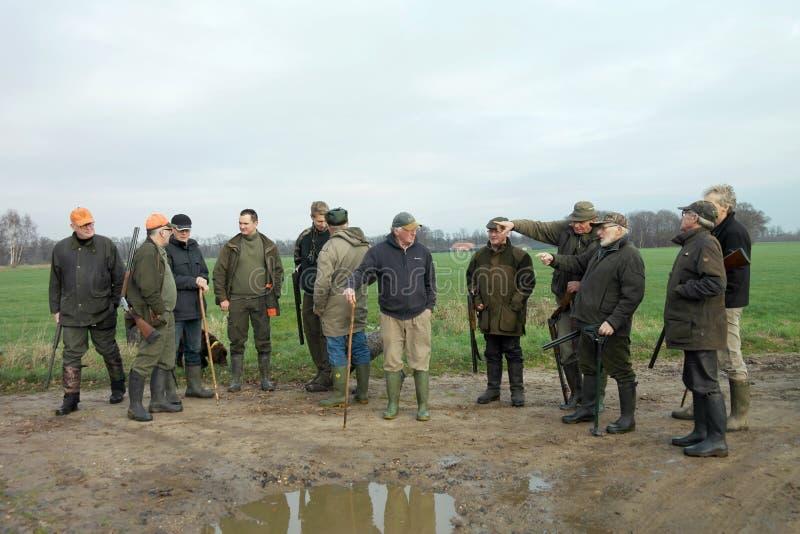 Ομάδα αρσενικών κυνηγών που συζητούν πού να πάει έπειτα Χειμώνας Κάτω Χώρες Κυνηγώντας ομάδα στοκ φωτογραφία