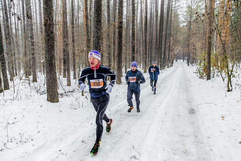 ομάδα αρσενικών δρομέων που τρέχουν το χιονώδες δάσος, πτώσεις χιονιού στοκ φωτογραφία με δικαίωμα ελεύθερης χρήσης