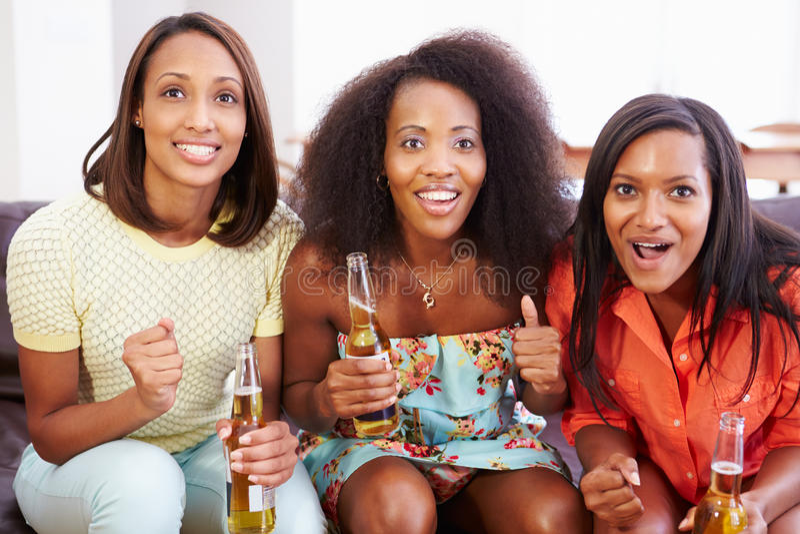 Ομάδα γυναικών που κάθονται στον καναπέ που προσέχει τη TV από κοινού στοκ φωτογραφίες