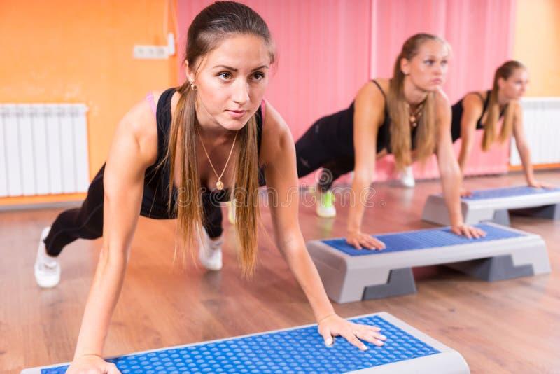 Ομάδα γυναικών που κάνουν τις ασκήσεις σανίδων στην κατηγορία βημάτων στοκ φωτογραφία με δικαίωμα ελεύθερης χρήσης