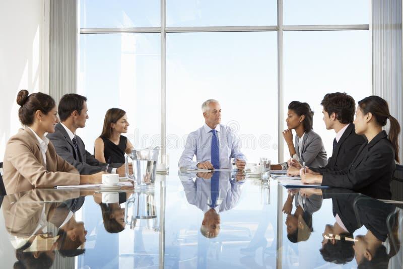 Ομάδα επιχειρηματιών που έχουν τη συνεδρίαση Συμβουλίου γύρω από τον πίνακα γυαλιού στοκ φωτογραφία με δικαίωμα ελεύθερης χρήσης