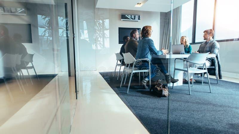 Ομάδα επιχειρηματιών που διοργανώνουν τη συζήτηση στη αίθουσα συνδιαλέξεων στοκ εικόνα