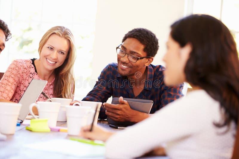 Ομάδα επιχειρηματιών που κάθονται τον πίνακα στη συνεδρίαση στοκ εικόνα