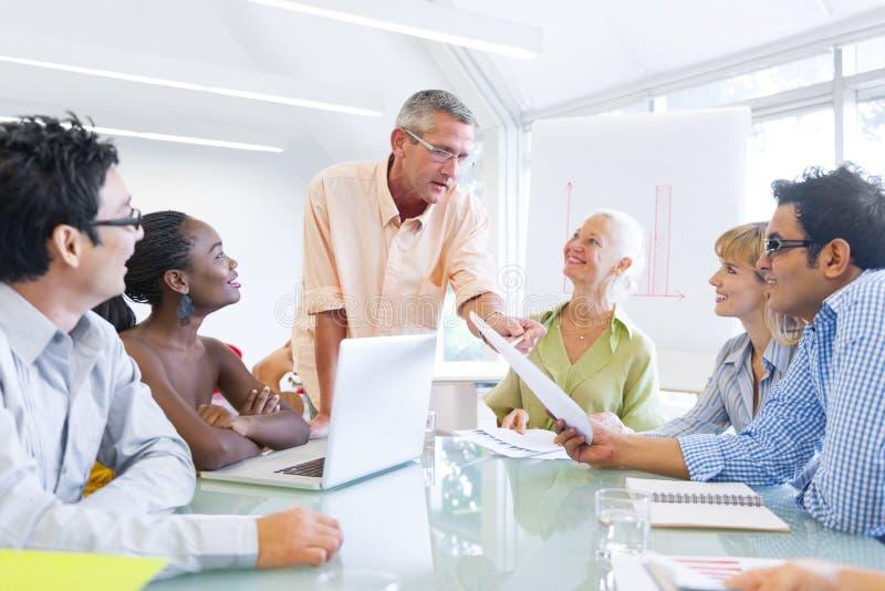 Ομάδα επιχειρηματιών που μαθαίνουν με τη βοήθεια του συμβούλου τους στοκ εικόνα
