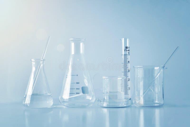 Ομάδα εργαστηριακών γυαλικών στον πίνακα, συμβολική της επιστήμης στοκ εικόνα