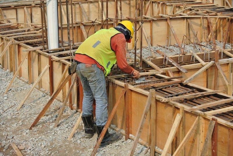 Ομάδα εργατών οικοδομών που κατασκευάζουν τον εγκιβωτισμό επίγειων ακτίνων στοκ φωτογραφία