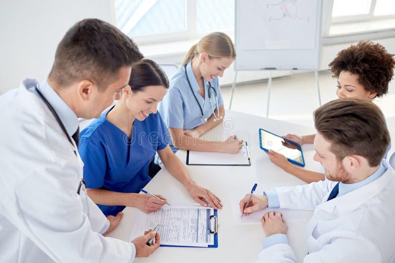 Ομάδα ευτυχών γιατρών που συναντιούνται στο γραφείο νοσοκομείων στοκ φωτογραφίες