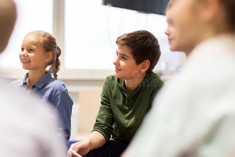 Ομάδα ευτυχών παιδιών ή φίλων που μαθαίνουν στο σχολείο στοκ εικόνα με δικαίωμα ελεύθερης χρήσης