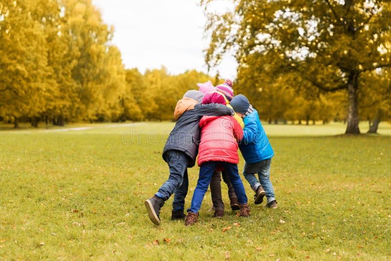 Ομάδα ευτυχών παιδιών που αγκαλιάζουν στο πάρκο φθινοπώρου στοκ εικόνα με δικαίωμα ελεύθερης χρήσης