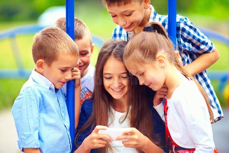 Ομάδα ευτυχών παιδιών που παίζουν τα παιχνίδι online μαζί, υπαίθρια στοκ εικόνες
