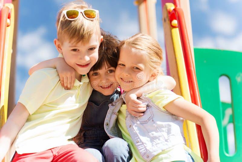 Ομάδα ευτυχών παιδιών στην παιδική χαρά παιδιών στοκ εικόνα με δικαίωμα ελεύθερης χρήσης