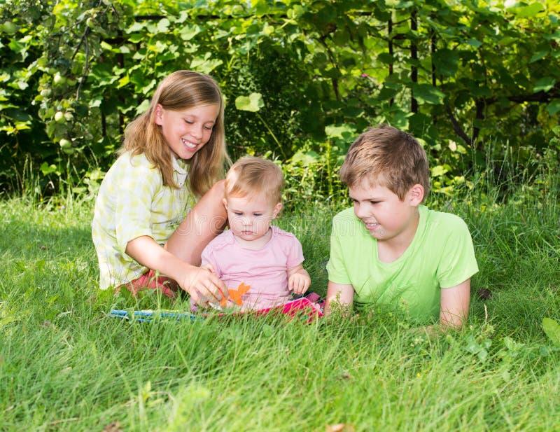 Ομάδα ευτυχών παιδιών υπαίθρια Δύο παιδιά και ένα playi κοριτσάκι στοκ φωτογραφίες