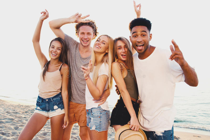 Ομάδα ευτυχών φίλων που έχουν τη διασκέδαση στην ωκεάνια παραλία στοκ εικόνα