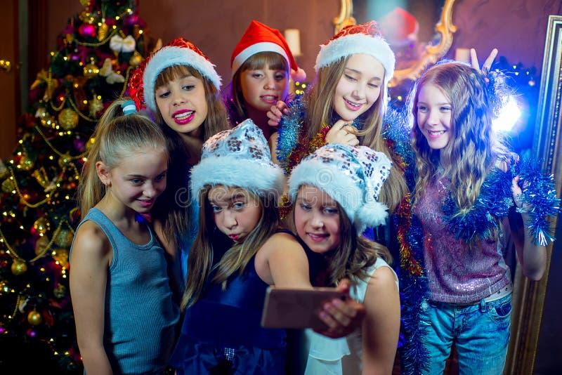 Ομάδα εύθυμων νέων κοριτσιών που γιορτάζουν τα Χριστούγεννα Selfie στοκ φωτογραφίες